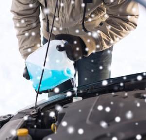 closeup of man pouring antifreeze into car